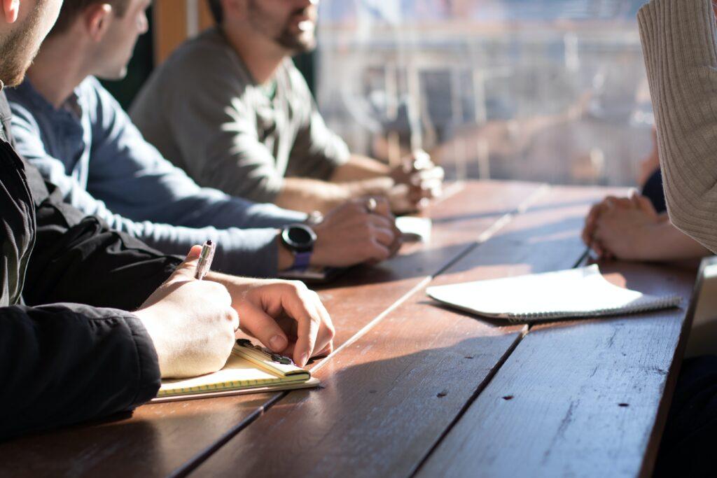 vijf mensen zitten op een bureau een marketingcommunicatieplan te bespreken, met blocnotes open geschreven