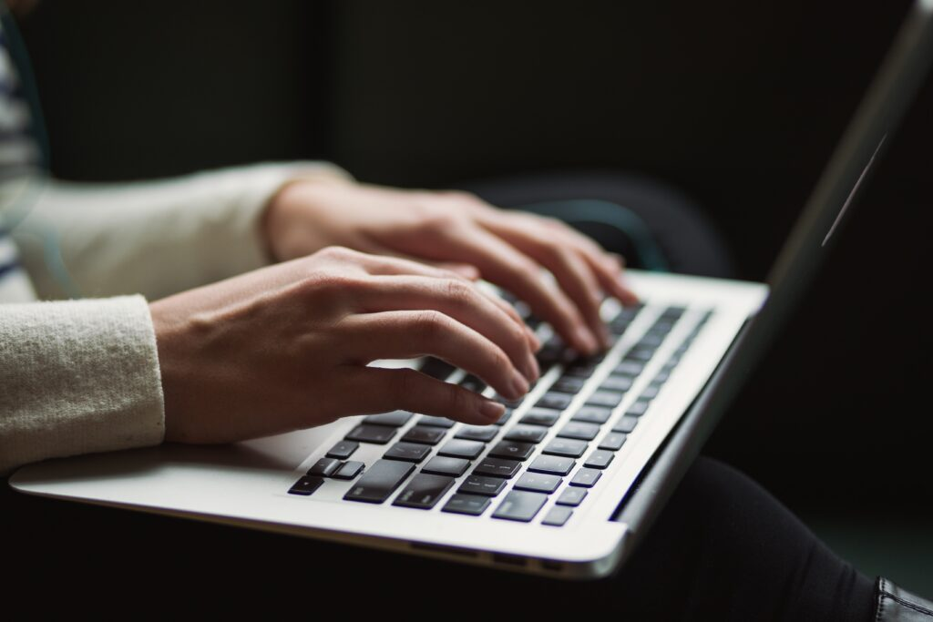 woman in jumper working on a content revision, typing into laptop