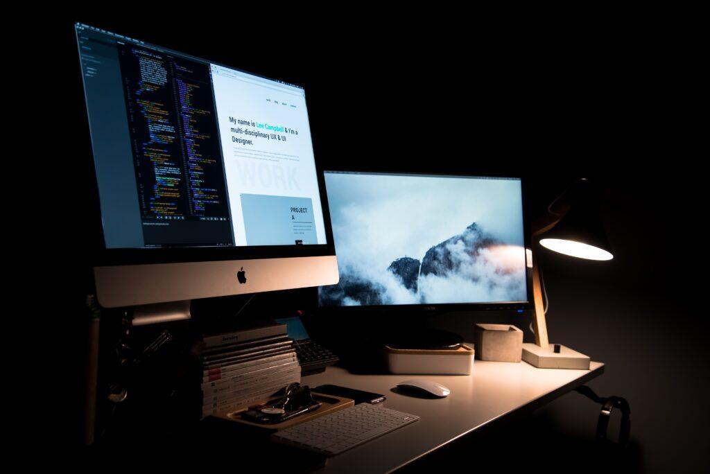 dubbele laptopschermen op en in het donker, bij een webdesignbureau