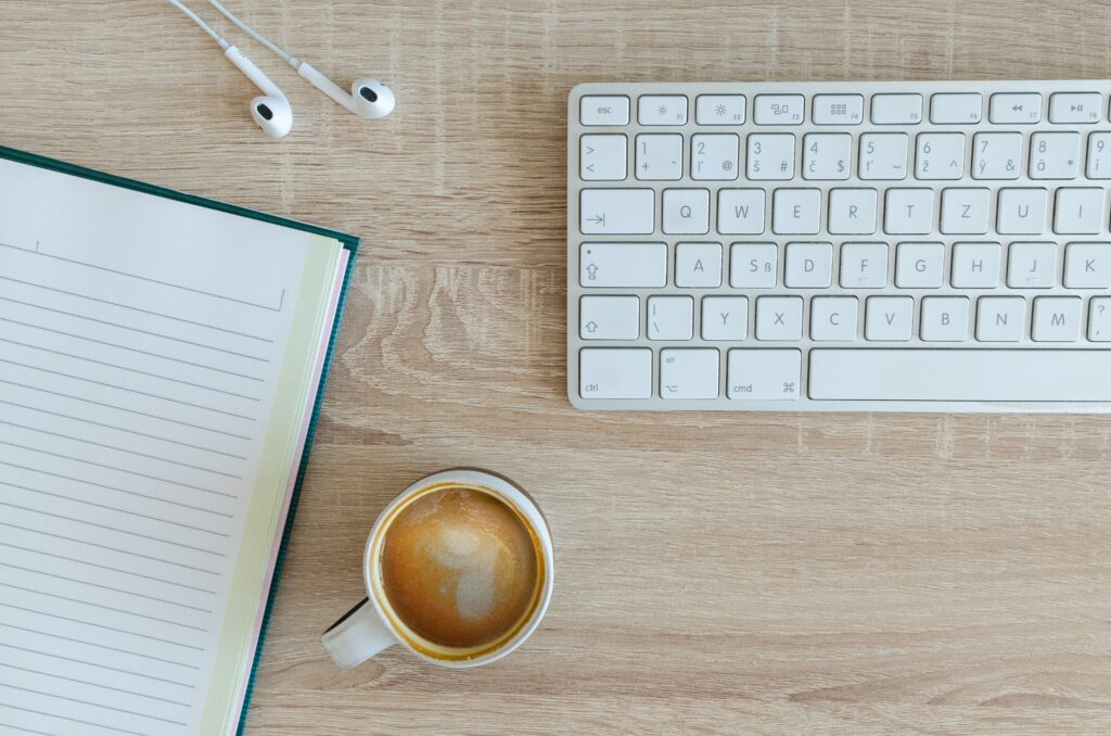 Coffee, notepad, white keyboard, and whiteheadphones on a brown desk, ready for a content revision
