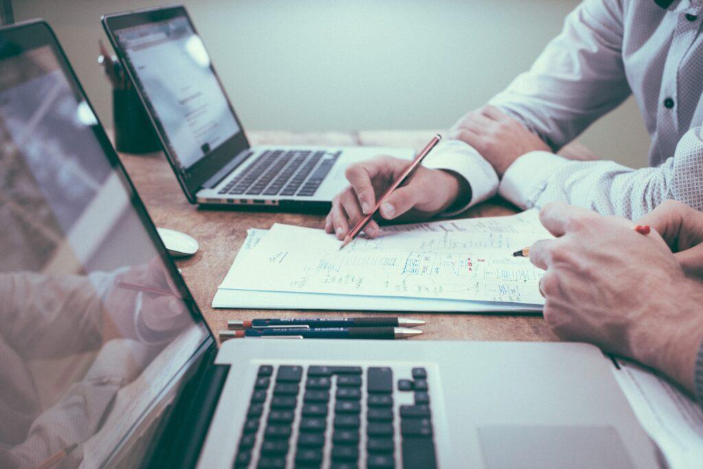 twee mensen die op laptops werken, discussiëren over contentcreatie