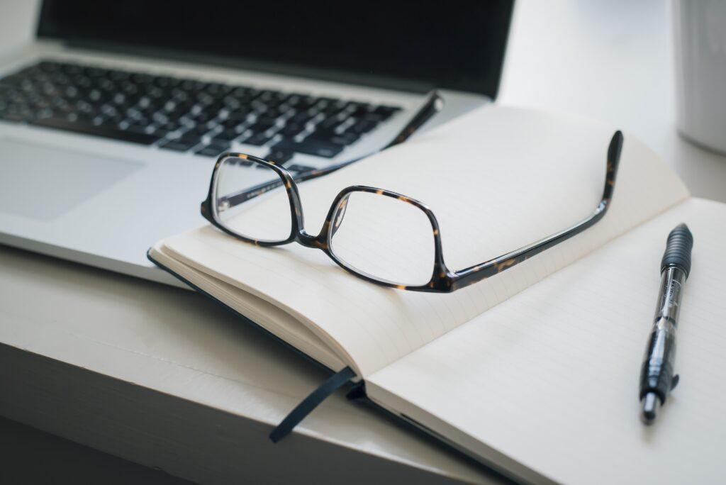 Notitieboekje open met bril en pen op, tegen laptop, bezig met contentcreatie